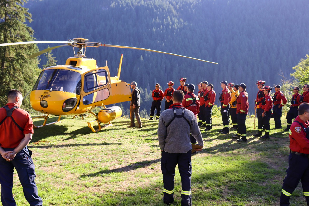 A group of District of North Vancouver firefighters in red wildfire fighting gear stand by a yellow helicopter