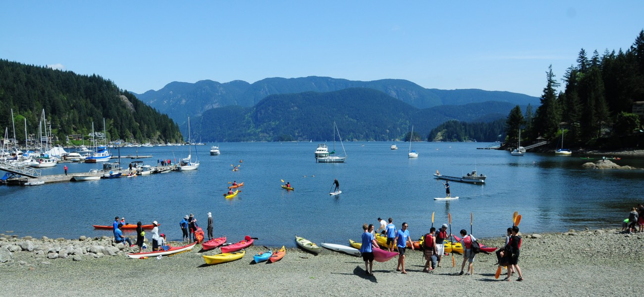 A group of kayakers on the beach in Deep Cove