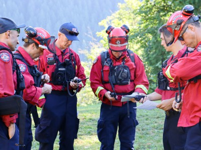 A group of DNVFRS firefighters in wildfire fighting gear stand in a circle coordinating radios