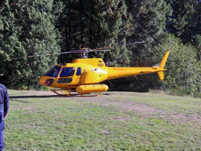 A yellow Talon helicopter in a field prepares for takeoff.