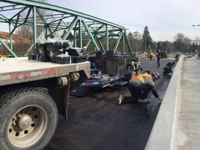 Workers waterproofing the bridge deck