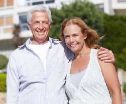 Senior couple standing in front of their home