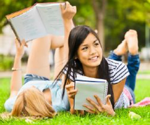 Students reading books in a park