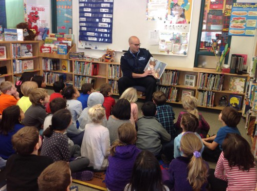 A member of the DNV fire department reading to a group of children
