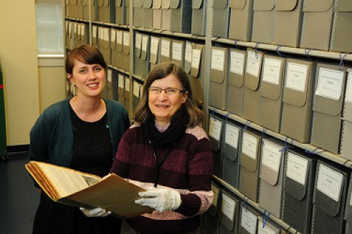 Two archive staff members standing in front of a book case