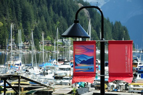 Street light with decorate banner in front of Deep Cove marina